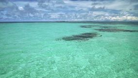 与在底下一些黑暗石头的清楚的绿松石水,掀动由蓝天决定 股票录像
