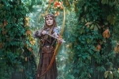 与在手中弓的妇女猎人,瞄准在他的牺牲者在森林亚马逊里 免版税库存图片