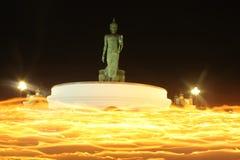 与在手中被点燃的蜡烛的结构在寺庙附近 库存图片