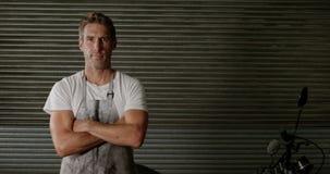 与在摩托车修理车库横渡的胳膊的男性技工身分4k 股票视频