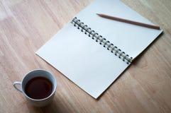 与在木桌上的咖啡杯一起使用 免版税库存图片