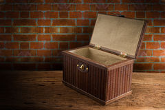 与在木桌面点燃的开放的老木胸口反对难看的东西 免版税库存图片