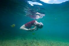 与在水面下一只红色野兽的俏丽的信奉瑜伽者跳舞 免版税图库摄影