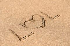 与在沙子写的心脏标志的LOL 免版税库存照片