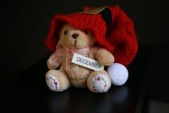 与在深黑色背景隔绝的红色圣诞节帽子的逗人喜爱的玩具熊 库存照片