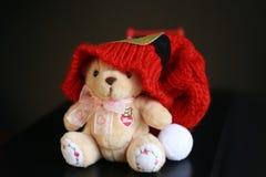 与在深黑色背景隔绝的红色圣诞节帽子的逗人喜爱的玩具熊 库存图片