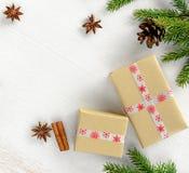 与在牛皮纸包裹的礼物盒的圣诞卡构成,冷杉分支与锥体 免版税图库摄影