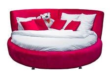 与在白色和白色玩具熊的圆的红色床隔绝的枕头 免版税库存图片