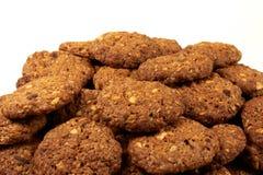 与在白色背景和坚果的谷物生物饼干隔绝的巧克力片 免版税库存照片