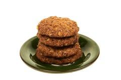 与在白色背景的一块绿色板材和坚果的生物谷物饼干隔绝的巧克力片 库存图片
