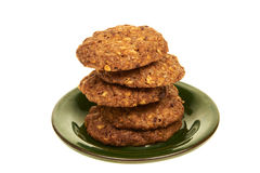 与在白色背景的一块绿色板材和坚果的谷物生物饼干隔绝的巧克力片 库存图片