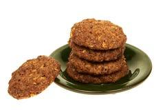 与在白色背景的一块绿色板材和坚果的谷物饼干隔绝的巧克力片 免版税库存照片