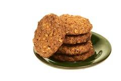 与在白色背景的一块绿色板材和坚果的谷物饼干隔绝的巧克力片 库存图片