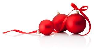 与在白色背景隔绝的丝带弓的三个红色圣诞节装饰中看不中用的物品 免版税库存照片