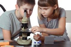 与在白色背景隔绝的显微镜的女孩和男孩十几岁 免版税库存照片