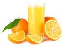 与在白色背景隔绝的橙色和绿色叶子的橙汁 在玻璃的汁液 免版税库存图片