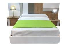 与在白色背景隔绝的床头柜的双人床 免版税库存照片