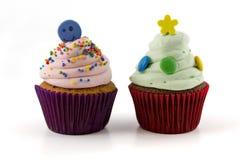 与在白色背景隔绝的桃红色和绿色奶油的杯形蛋糕 免版税库存照片