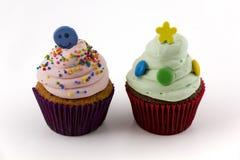 与在白色背景隔绝的桃红色和绿色奶油的杯形蛋糕 图库摄影