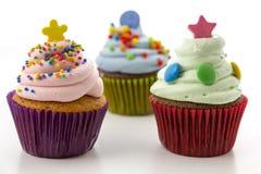 与在白色背景隔绝的桃红色和绿色奶油的杯形蛋糕 库存图片