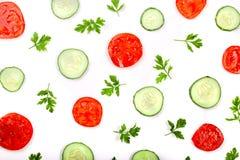 与在白色背景隔绝的荷兰芹叶子的黄瓜和蕃茄切片 顶视图 库存照片
