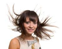与在白色背景隔绝的长的吹的头发的女孩画象 库存照片