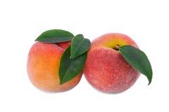 与在白色背景隔绝的绿色叶子的两三个水多的桃红色黄色桃子 健康夏天快餐 库存图片