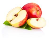 与在白色背景隔绝的绿色叶子的切的红色苹果 免版税库存照片