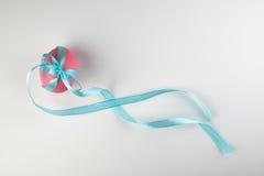 与在白色隔绝的一把蓝色弓的桃红色复活节彩蛋 免版税库存照片
