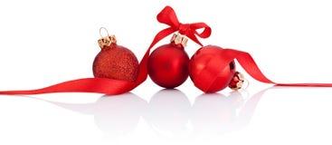 与在白色隔绝的丝带弓的三个红色圣诞节球 免版税库存照片