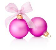 与在白色隔绝的丝带弓的两个桃红色圣诞节中看不中用的物品 免版税库存图片