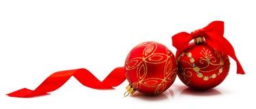 与在白色隔绝的丝带的两个红色圣诞节球 库存照片