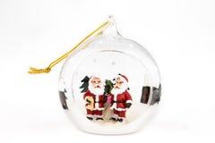 与在白色隔绝的圣诞老人里面的透明圣诞节球 库存图片