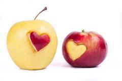 与在白色隔绝的心脏的两个苹果 免版税库存图片