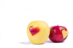 与在白色隔绝的心脏的两个苹果 库存图片