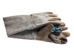 与在白色隔绝的板钳的老皮革工作手套 免版税库存照片