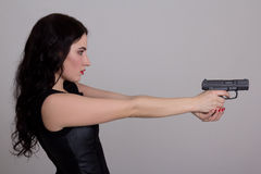 与在白色隔绝的枪的严肃的性感的妇女射击 免版税库存照片