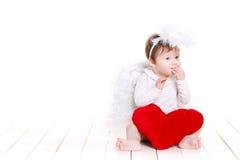 与在白色隔绝的红色心脏的一点天使 库存图片