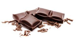 与在白色隔绝的面包屑的黑暗的巧克力块堆 免版税库存图片