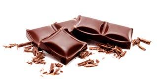 与在白色隔绝的面包屑的黑暗的巧克力块堆 免版税库存照片