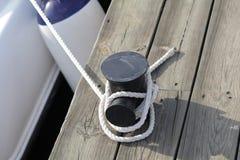 与在磁夹板附近被栓的一个被打结的末端的停泊绳索 库存照片