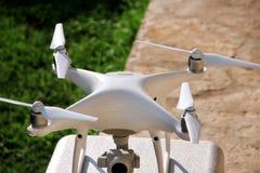 与在立场的数字照相机准备好的4K的白色quadcopter寄生虫在空气离开飞行拍照片,记录英尺长度 免版税图库摄影