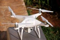 与在立场的数字照相机准备好的4K的白色quadcopter寄生虫在空气离开飞行拍照片,记录英尺长度 免版税库存图片