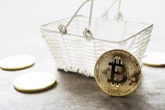 与在网上手提篮隐藏货币的金黄bitcoin硬币 免版税库存照片