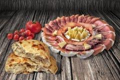 与在老破裂的木背景和被发酵的皮塔小面包干被撕毁的大面包设置的束的开胃菜美味盘蕃茄 库存图片