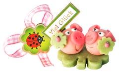 与在背景和好运的两头小杏仁饼猪(用德语)写的苜蓿叶形立交路口 库存图片