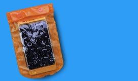 与在蓝色背景隔绝的水滴的橙色防水手机盒 PVC邮编锁袋子保护手机或impor 免版税库存图片