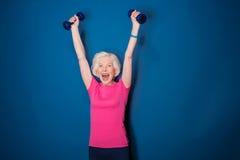 与在蓝色隔绝的哑铃的资深健身妇女训练 库存照片