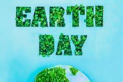 与在行星模型的绿色新草新芽和部分的概述的创造性的概念世界地球日上写字在蓝色背景的 保存p 免版税图库摄影