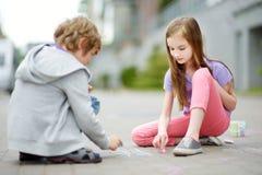 画与在边路的五颜六色的白垩的两个愉快的孩子 小孩子的夏天活动 免版税图库摄影